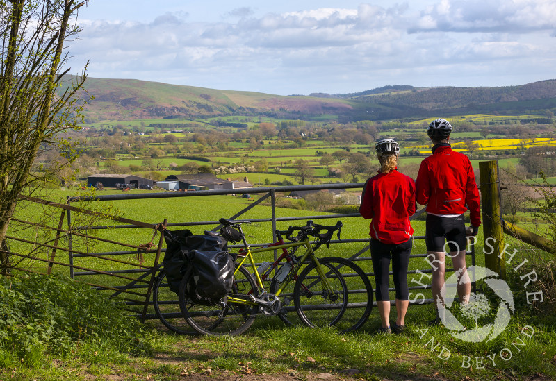 Two cyclists stop to admire the view towards the Long Mynd, seen near Linley Hill, Shropshire.