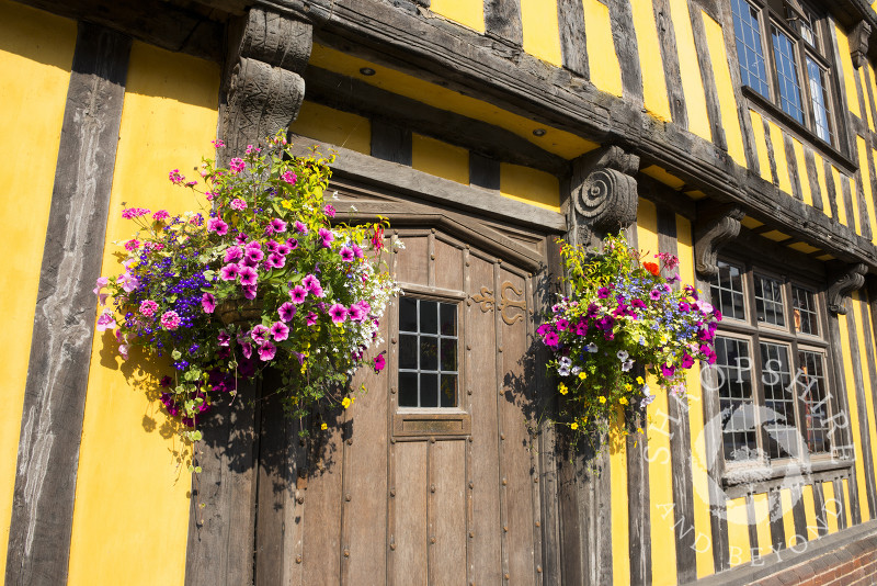 Hanging baskets outside half-timbered house in Broad Street, Ludlow, Shropshire, England.