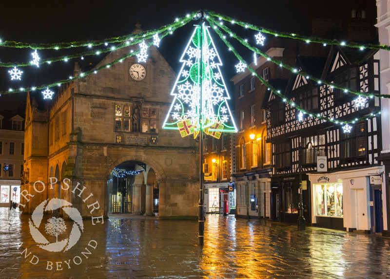 Christmas lights reflected in rain-covered flagstones in the Square, Shrewsbury, Shropshire.