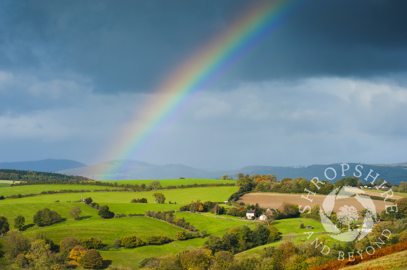 Autumn rainbow over Round Oak, seen from Hopesay Common, near Craven Arms, Shropshire, England.