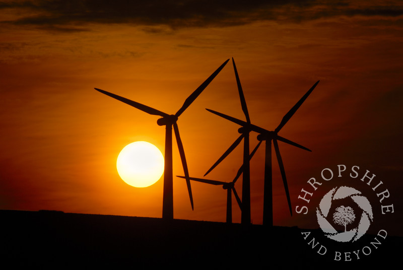 The sun goes down behind the turbines at Carno Wind Farm in Powys, Mid Wales.
