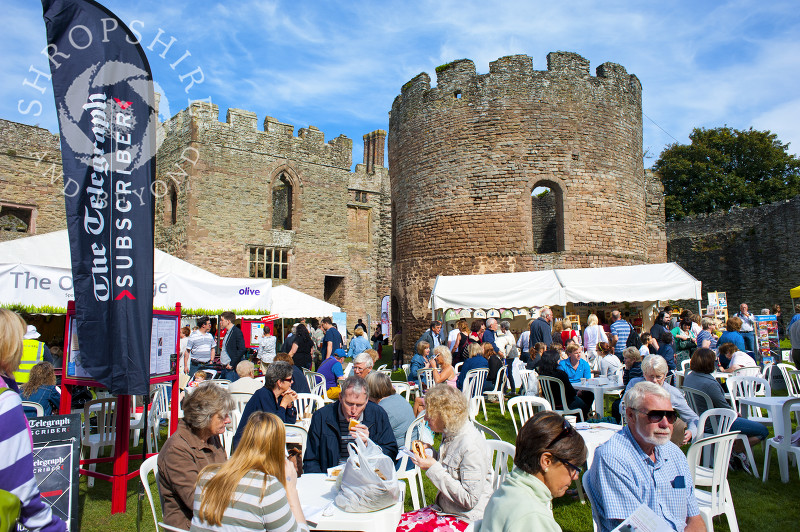Visitors enjoy the sunshine in the grounds of Ludlow Castle during Ludlow Food Festival, Shropshire, England.