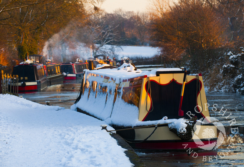 Late afternoon sunlight glistens on the winter snow along the Llangollen Canal at Ellesmere, Shropshire, England.
