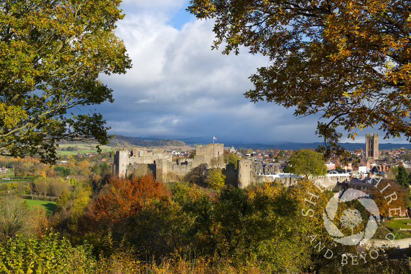 Autumn colours frame Ludlow Castle and St Laurence's Church as a shower of rain approaches from over Brown Clee Hill, Ludlow, Shropshire,  England.