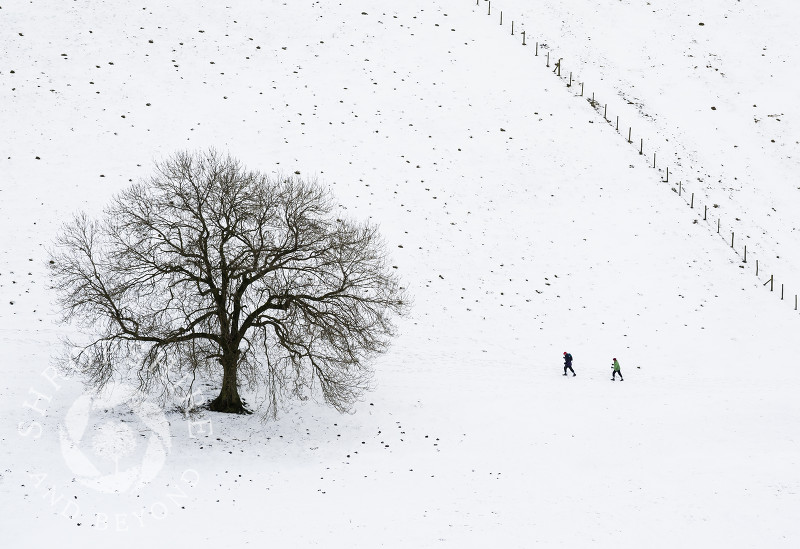 Walkers in snow beneath Gaer Stone, near Church Stretton, Shropshire, England.