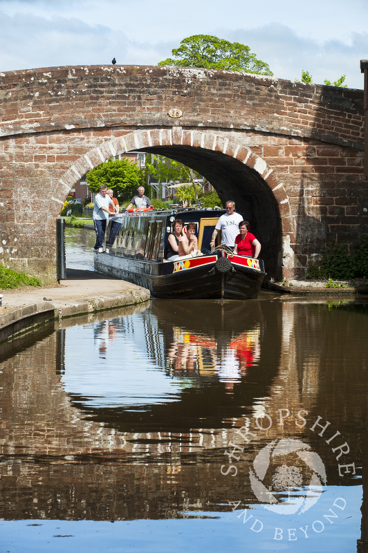 A canal boat and bridge are reflected in the waters of the Shropshire Union Canal at Market Drayton, Shropshire, England.