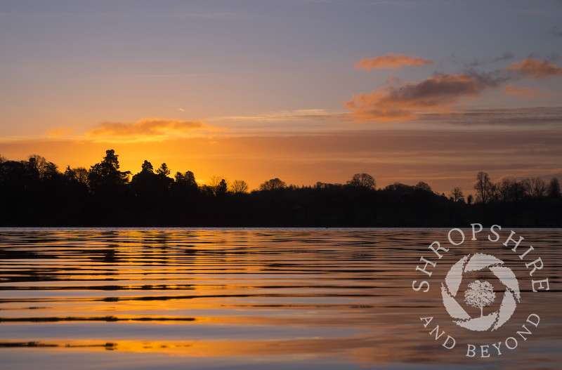 Sunrise highlights ripples on the Mere at Ellesmere, Shropshire.