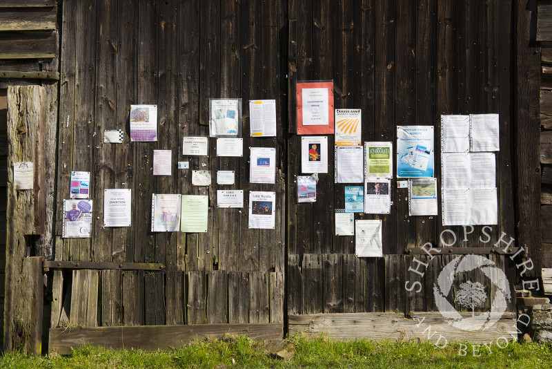 The village noticeboard on the side of an old barn in Hopesay, near Craven Arms, Shropshire, England.