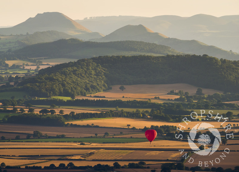 A hot air balloon over Shropshire, seen from the Wrekin, with the Stretton Hills in the distance.