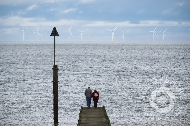 An elderly couple stand on a jetty at Llandudno, Conwy, Wales and look out across the sea towards Gwynt y Mor wind farm.
