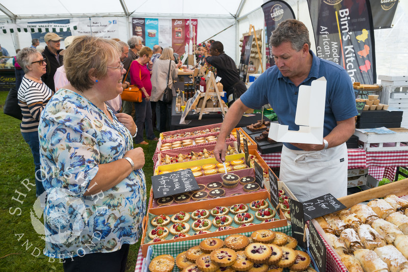 A visitor makes a selection from the Love Patisserie stall at Ludlow Food Festival, Shropshire.