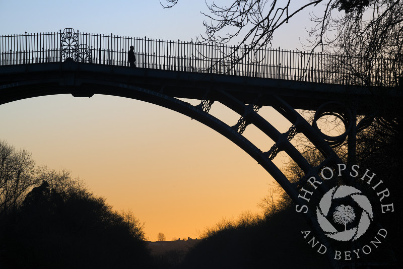 A lone figure on the Iron Bridge at sunrise, Ironbridge, Shropshire, England.