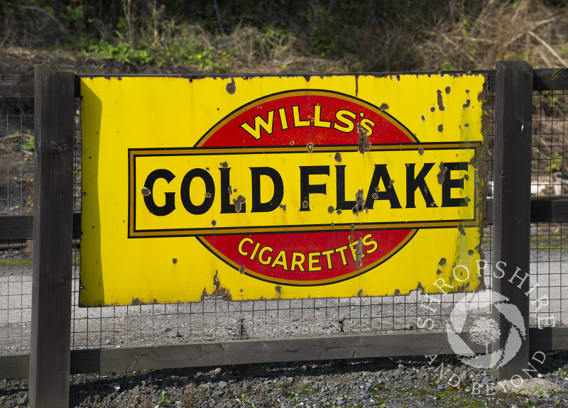 Vintage enamel sign advertising Wills's Gold Flake Cigarettes at Highley Station, Shropshire, on the Severn Valley Railway heritage line.
