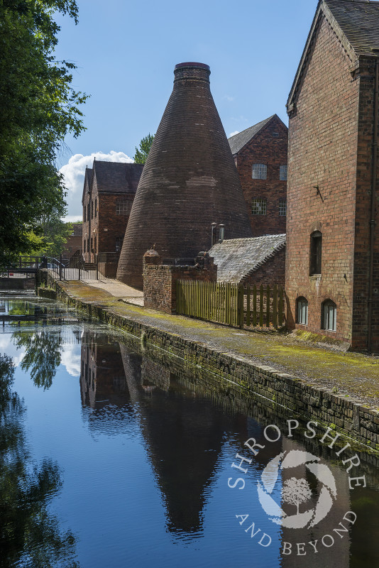 A bottle kiln at Coalport China Museum reflected in the water of the Shropshire Canal at Coalport, near Ironbridge, Shropshire.