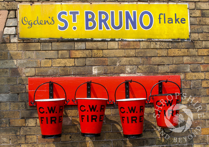 Fire buckets and advertising signs on the platform at Hampton Loade Station, Severn Valley Railway, Shropshire, England.