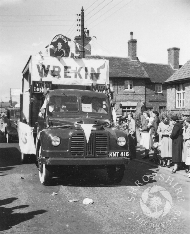The Wrekin Brewery float passes the Beehive public house in Shifnal, Shropshire, during the town's annual carnival in the 1950s.