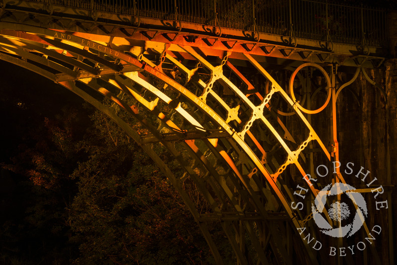 The illuminated cast iron structure of the Iron Bridge at Ironbridge, Shropshire, England.