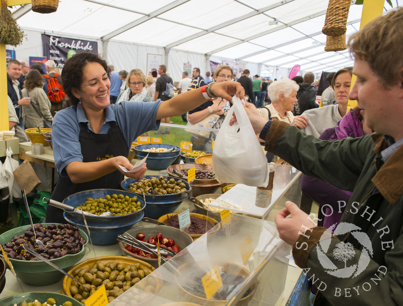 A shopper buys olives at the Olive Press stall, 2014 Ludlow Food Festival, Shropshire, England.