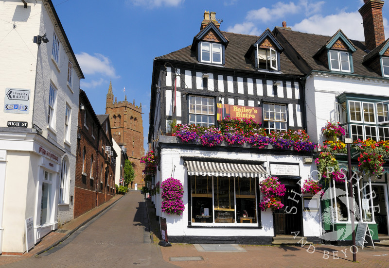 Flower display and restaurant in High Street, overlooked by St Leonard's Church, in Bridgnorth, Shropshire, England.