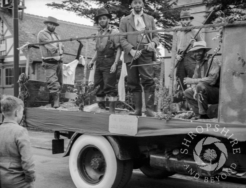 The Broadway Brewery Gold Diggers float passes the Fire Station in Shrewsbury Road, Shifnal, Shropshire, during the carnival procession in the 1950s.