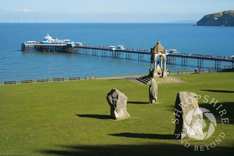 Happy Valley Gardens stone circle and Victorian drinking fountain looking to Llandudno Pier, North Wales.