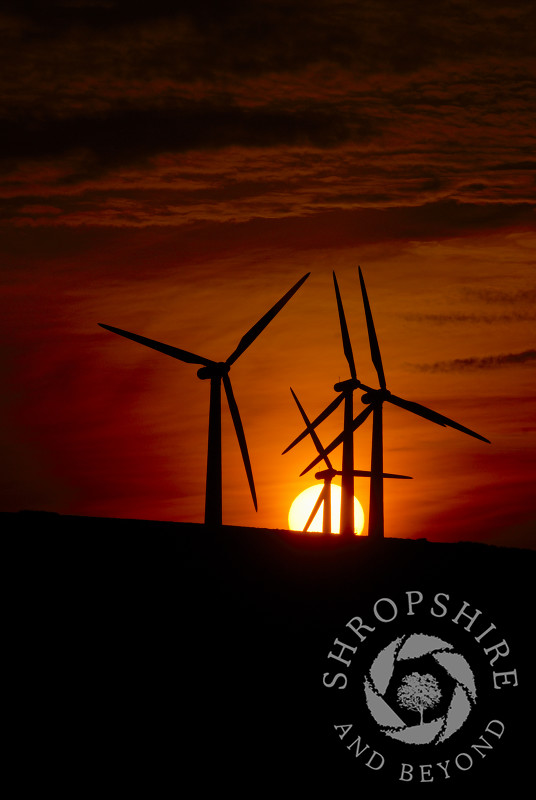 The sun goes down behind the turbines at at Carno Wind Farm in Powys, Mid Wales.