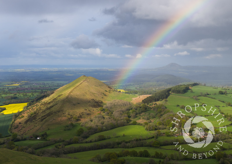 A rainbow beside the Lawley with the Wrekin on the horizon, seen from Caer Caradoc, Shropshire.